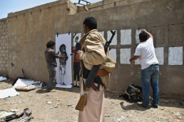 An armed man looks at graffiti artists spraying on a wall to commemorate the victims who were killed in Saudi-led coalition airstrikes in Sanaa, Yemen, Monday, May 18, 2015. Saudi-led airstrikes targeting Yemen's Shiite rebels resumed early on Monday in the southern port city of Aden after a five-day truce expired amid talks on the war-torn country's future that were boycotted by the rebels. (AP Photo/Hani Mohammed)