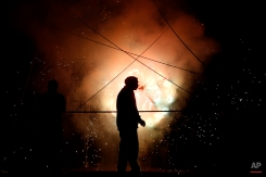 """A pyrotechnics worker smokes a cigarette during a fireworks show, Sunday, May 10, 2015, in Tepexpan, Mexico. Tepexpan is closing out its annual two-week celebration honoring """"El Senor de Gracias,"""" the town's patron saint. (AP Photo/Julio Cortez)"""