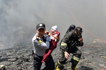 A police officer and a fire fighter help child victim of an apartment building fire in Baku, Azerbaijan, Tuesday, May 19, 2015. Azerbaijani officials say 16 people have died and more than 50 have been injured in a fire at an apartment building in Baku, the capital. The massive fire quickly engulfed 16-story apartment building Tuesday and took hours to contain. Azerbaijan's chief prosecutor, Zakir Garalov, said the bad quality of plastic paneling covering the building contributed to the fire and a criminal probe has been launched to determine the culprits. (AP Photo/Orxan Azim)