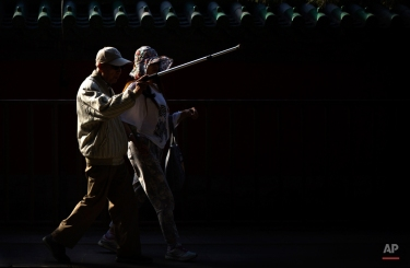 A man points with his walking stick while strolling through Ritan Park in Beijing, Tuesday, May 19, 2015. The area, which was once the site of ritual sacrifices to the sun by China's emperors, is now a public park. (AP Photo/Mark Schiefelbein)