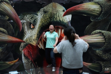 A Chinese woman shares a light moment with her friend as she poses with a 3-D painting of a dinosaur at an art exhibition at a shopping mall in Beijing, China, Wednesday, May 13, 2015. (AP Photo/Andy Wong)