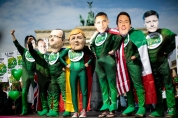 Climate activists in green costumes and with masks of the G7 leaders Japanese Prime Minister Shinzo Abe, Britain's Prime Minister David Cameron, French President Francois Hollande, German Chancellor Angela Merkel, US President Barack Obama, Italian Prime Minister Matteo Renzi and Canadian Prime Minister Stephen Harper, from left, attend a protest in front of the Brandenburg Gate near a building hosting the 'Petersberg Climate Dialogue' conference in Berlin, Germany, Tuesday, May 19, 2015. The demonstrators demand a 100 percent clean energy. (AP Photo/Markus Schreiber)