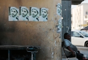 """A man watches Bahraini anti-government protesters marching in support of jailed opposition leader Sheikh Ali Salman, seen in pictures on the wall, in Bilad al-Qadeem, Bahrain, Tuesday, May 19, 2015. Protesters shouted slogans and demanded democracy and freedom for Salman, a Shiite cleric who leads the largest political opposition group, and is due in court Wednesday on charges of trying to overthrow the government. Arabic writing on the signs read: """"We will not be defeated."""" (AP Photo/Hasan Jamali)"""