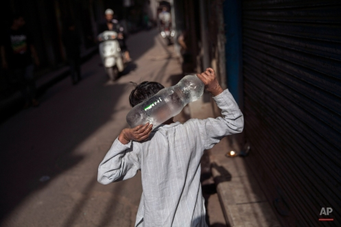 An Indian boy carries a bottle filled with cold water as he goes to a market on a hot day in New Delhi, India, Monday, May 18, 2015. An intense heat-wave continues to grip several parts of north India with most of the cities crossing 40 degrees Celsius (104 degrees Fahrenheit) mark. (AP Photo/Tsering Topgyal)