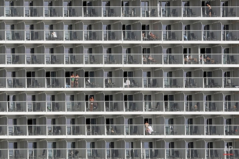 Vacationers are seen on cabin balconies of the 347-meter Quantum of the Seas cruise ship docked at the port of Piraeus near Athens, Monday, May 18, 2015. Greece's cash strapped government is examining ways to improve tax collection from the country's key tourism sector as it struggles to continue payments to bailout lenders. (AP Photo/Petros Giannakouris)