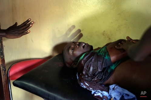 A demonstrator seriously wounded by live ammunition waits for treatment in a small clinic in the Musaga district of Bujumbura, Burundi, Monday, May 4, 2015. Anti-government demonstrations resumed in Burundi's capital after a weekend pause as thousands continue to protest the president's decision to seek a third term. (AP Photo/Jerome Delay)