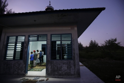 Muslim Rohingya men perform evening prayer at a mosque in Langsa, Aceh province, Indonesia, Monday, May 18, 2015. Boatloads of more than 2,000 migrants of ethnic Rohingya Muslims fleeing persecution in Myanmar and Bangladeshis trying to escape poverty have landed in Indonesia, Malaysia and Thailand in recent weeks. Aid groups estimate that thousands more are stranded at sea after a crackdown on human traffickers prompted captains and smugglers to abandon their human cargo. (AP Photo/Binsar Bakkara)