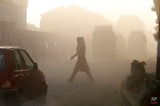 A Kashmiri woman covers her face as she crosses a dusty road in Srinagar, India, Wednesday, May 6, 2015. (AP Photo/Mukhtar Khan)