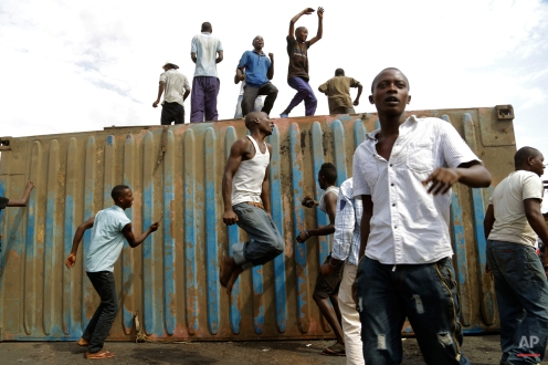 Demonstrators climb onto a container used as a barricade in the Cibitoke neighborhood of Bujumbura, Burundi, Tuesday, May 19, 2015. Protesters have been demonstrating for the last three weeks opposing the president's bid for a third term. (AP Photo/Jerome Delay)