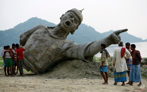 Indian people stand near a part of a bronze statue of Lachit Borphukan, an army general from the northeastern state of Assam, set to be installed in the middle of the Brahmaputra on a podium, in Gauhati, India, Thursday, May 21, 2015. (AP Photo/Anupam Nath)