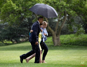 President Barack Obama shares his umbrella with White House Deputy Chief of Staff Anita Decker Breckenridge, right, and White House Senior Adviser Valerie Jarrett, center, during a downpour during the walk from Marine One helicopter across the South Lawn to the Oval Office of the White House in Washington, Monday, May 18, 2015, as they return from Camden, N.J., where the president visited with local law enforcement, met with young people in the Camden community and toured the Real-Time Tactical Operation Intelligence Center at the Camden County Police Department headquarters. Obama also announced that he is prohibiting the federal government from providing some military-style equipment to local departments and putting stricter controls on other weapons and gear distributed to law enforcement. (AP Photo/Carolyn Kaster)