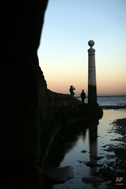 A couple take photographs at the Cais das Colunas dock by the Tagus riverbank, in Lisbon, Friday, May 15, 2015. (AP Photo/Francisco Seco)