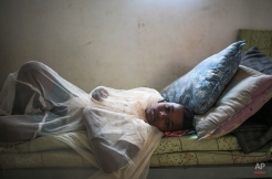Abo Bakr Mohammed, 12, who suffers from epilepsy, covers himself with a mosquito net in his family's room, in an under-construction orphanage that has been turned into a transit centre for Yemeni refugees, in Obock, northern Djibouti, Tuesday, May 19, 2015. According to UNHCR, at least 1000 Yemeni refugees seeking asylum or with no prior visas have arrived to Obock since the beginning of the Saudi-led airstrikes. At least 3000 others have arrived to Djibouti city. (AP Photo/Mosa'ab Elshamy)
