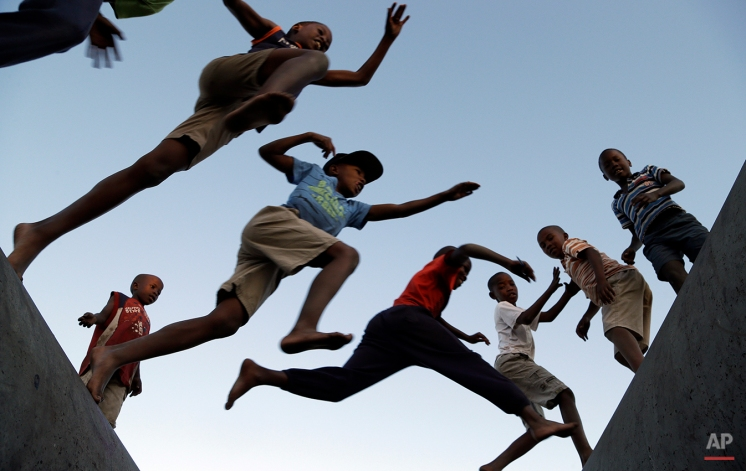 Young boys jumps from one concrete drainage pipe to another in a park in Katlehong, south of Johannesburg, South Africa, Wednesday, May 6, 2015. (AP Photo/Themba Hadebe)