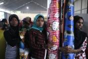 Rohingya women hold sleeping mats at a temporary shelter in Langsa, Aceh province, Indonesia, Tuesday, May 19, 2015. The country has sheltered more than 1,000 Rohingya and Bangladeshi migrants who washed onto Aceh and North Sumatra provinces last week. (AP Photo/Binsar Bakkara)