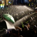 Police officers spray protesters as they try to march at a rally to commemorate the first anniversary of the Sewol ferry sinking in Seoul, South Korea, Thursday, April 16, 2015. With public anger and grief raw one year after a ferry sinking killed 304 people, South Korea's president promised on Thursday to raise the submerged vessel, even as relatives of the victims snubbed her appearance at a mourning ceremony. (AP Photo/Lee Jin-man)