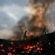Impoverished Indians walk next to burning trash at Dharavi, one of the world's largest slums, in Mumbai, India, Thursday, April 9, 2015. Air pollution kills millions of people every year, including more than 627,000 in India, according to the World Health Organization. The WHO puts 13 Indian cities in the world's 20 most polluted. (AP Photo/Rafiq Maqbool)