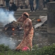 A woman weeps during the cremation of a victim of Saturday's earthquake, at the Pashupatinath temple, on the banks of Bagmati river, in Kathmandu, Nepal, Sunday, April 26, 2015. The earthquake centered outside Kathmandu, the capital, was the worst to hit the South Asian nation in over 80 years. It destroyed swaths of the oldest neighborhoods of Kathmandu, and was strong enough to be felt all across parts of India, Bangladesh, China's region of Tibet and Pakistan. (AP Photo/Bernat Armangue)