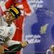 Mercedes driver Lewis Hamilton, of Britain, sprays rose water on the podium after winning the Bahrain Formula One Grand Prix at the Formula One Bahrain International Circuit in Sakhir, Bahrain, Sunday, April 19, 2015. (AP Photo/Luca Bruno)
