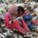 A Pakistani scavenger girl writes on a notebook she collected from a garbage, while another girl sits next to her in Lahore, Pakistan, Wednesday, April 1, 2015. Thousands of children pick recyclable items from waste dumping points to earn living for their poor families. (AP Photo/K.M. Chaudary)