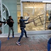 A protestor breaks a window at a store after a rally for Freddie Gray, Saturday, April 25, 2015, in Baltimore. Gray died from spinal injuries about a week after he was arrested and transported in a police van. (AP Photo/Patrick Semansky)