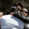 Mourners hug during a funeral service for Armoni Keavon Sexton, a promising New Jersey high school basketball player who was killed in a drive-by shooting, Monday, April 27, 2015, in Paterson, N.J. Sexton, 15, a top scorer and rebounder at the Paterson Charter School for Science for Science and Technology, was killed and three others were injured in the shooting in Paterson on April 18. (AP Photo/Mel Evans)