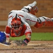 Philadelphia Phillies catcher Carlos Ruiz dives while trying to tag New York Mets' Lucas Duda, who returned to the plate after failing to tag it during the fifth inning of a baseball game in New York, Tuesday, April 14, 2015. Phillies manager Ryne Sandberg utilized a manager's challenge on the play, but Duda was ruled safe. (AP Photo/Kathy Willens)