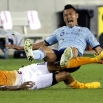 Sporting Kansas City's Roger Espinoza, right, falls as he is tackled by Houston Dynamo's Ricardo Clark, left, during the second half of an MLS soccer game Saturday, April 25, 2015, in Houston. The teams played to a 4-4- tie. (AP Photo/David J. Phillip)