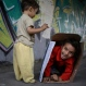 Yara, 5, and her brother Youssef, left, 16 months, hide inside a cardboard box as they play under a bridge while their mother sells tissue in Cairo, Egypt, Thursday, May 14, 2015. (AP Photo/Hassan Ammar)