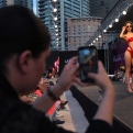 A member of the audience, left, takes a picture with her mobile phone as a model displays a creation as part of the Italian fashion label La Perla's Spring-Summer 2015 beachwear collection, during the summer fashion week at Saint George Yacht Club, in Beirut, Lebanon, Friday, May 22, 2015. (AP Photo/Hussein Malla)