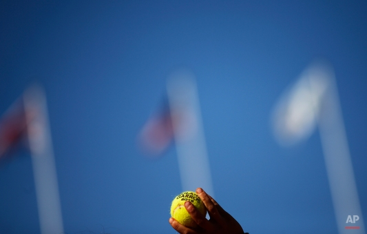 A ball-boy holds balls for the service in the semifinal match of the French Open tennis tournament between Serena Williams of the U.S. and Timea Bacsinszky of Switzerland at the Roland Garros stadium, in Paris, France, Thursday, June 4, 2015. (AP Photo/Christophe Ena)