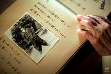 In this April 29, 2015 photo, Yoshiomi Yanai, a survived kamikaze pilot, looks at his last will and testament with his portrait photo which he shot as a kamikaze pilot in 1945 during an exclusive interview with the Associated Press at Tsukuba Naval Air Group Base in Kasama, Ibaraki Prefecture, north of Tokyo.(AP Photo/Eugene Hoshiko)