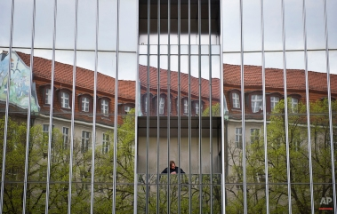 A man is reflected in the facade of the Axel Springer house in Berlin, April 29, 2013. (AP Photo/dpa, Ole Spata)