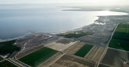 In this May 1, 2015 aerial photo, exposed lake bed of the Salton Sea dries out near Niland, Calif. San Diego and other Southern California water agencies will stop replenishing the lake in 2017, raising concerns that dust from the exposed lake bed will exacerbate asthma and other respiratory illness in a region whose air quality already fails federal standards. (AP Photo/Gregory Bull)