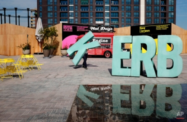 Ian, who works for Kerb, an organization that helps turn public spaces over to traders selling food, carries a letter to spell out Kerb as he prepares for traders to arrive in Cubitt Square, King's Cross, London, June 4, 2015. (AP Photo/David Azia)