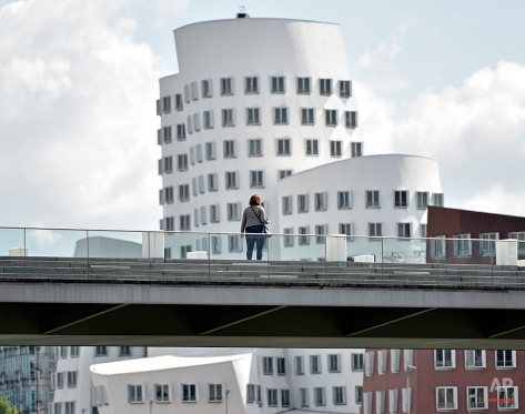A woman watches the leaning towers by star architect Frank Gehry at the media port in Duesseldorf, Germany, May 21, 2015. (AP Photo/Martin Meissner)