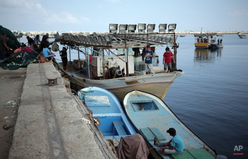 In this Friday, June 5, 2015 photo, Palestinian children play on a fishing boat as fishermen prepare their fishing nets at the sea port of Gaza City. (AP Photo/Khalil Hamra)