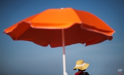 A woman sits next to an umbrella while looking out toward the ocean, June 16, 2015, in Folly Beach, S.C. (AP Photo/David Goldman)