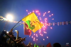 A demonstrator holds a banner of jailed Kurdish rebel leader Abdullah Ocalan, as a firework explodes behind, as supporters of pro-Kurdish Peoples's Democracy Party celebrate election results in Diyarbakir, southeastern Turkey, Monday, June 8, 2015. Turkey's long-ruling Justice and Development Party of President Recep Tayyip Erdogan has suffered strong losses in parliamentary elections that will force it to seek a coalition partner for the next government, but other parties vowed to resist any pact as election results flowed in Monday. (AP Photo/Emre Tazegul)