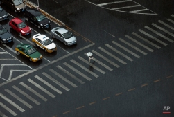 A woman holding an umbrella walks across a traffic intersection during a heavy rain storm in Beijing, China, June 17, 2015. (AP Photo/Andy Wong)