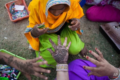 An Indian woman makes Mehndi designs on a customer's hand in New Delhi, India, Monday, June 8, 2015. Women use Mehndi for decoration and mainly for festive occasions, such as weddings, religious events and traditional ceremonies. (AP Photo/Tsering Topgyal)