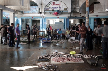 In this Friday, June 5, 2015 photo, Palestinians display fish for sale in the fish market of Gaza City. (AP Photo/Khalil Hamra)