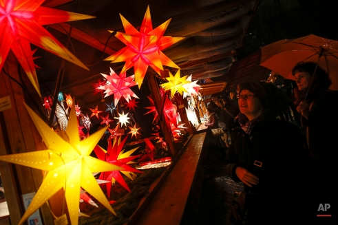Two women inspect advent stars at a shop in a Christmas market in Berlin, Dec. 4, 2013. (AP Photo/Markus Schreiber)