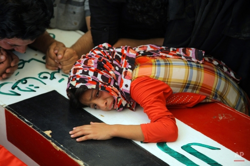 Zahra Mahmoud, 11, grieves on her father's coffin during the funeral procession of 15 militia members of a Shiite group, Asaib Ahl al-Haq, or League of the Righteous, who were killed in Beiji from fighting with Islamic State militants, according to their families, in Najaf, 100 miles (160 kilometers) south of Baghdad, Iraq, Monday, June 8, 2015. (AP Photo/Jaber al-Helo)