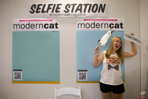 In this Saturday, June 6, 2015 photo, Kimberly Hampshire poses for photos at a selfie station during CatConLA in Los Angeles. The first-ever CatConLA brought the cat craze popularized online to life. (AP Photo/Jae C. Hong)