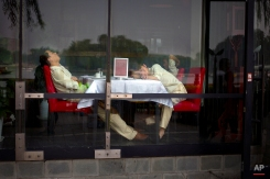 Waiters nap at a table as they wait for customers at a restaurant in Beijing, June 26, 2015. (AP Photo/Mark Schiefelbein)