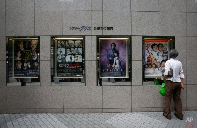 A man looks at one of the posters of stage performances displayed at a theater in Tokyo, Monday, June 8, 2015. (AP Photo/Shizuo Kambayashi)