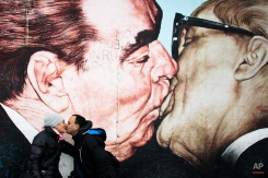 A couple, tourists from Mexico, kiss in front of the painting of former Soviet Leader Leonid Brezhnev and former East German leader Erich Honecker kissing by artist Dmitri Vrubel at the East Side Gallery, remains of the Berlin Wall, in Berlin, Germany, May 12, 2014. (AP Photo/Markus Schreiber)