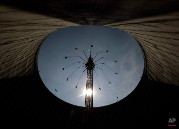 Visitors enjoy sunny weather at the 58 meter (190ft) high chairoplane on top of a former cooling tower in Kalkar, Germany, Aug. 13, 2012. (AP Photo/Frank Augstein)