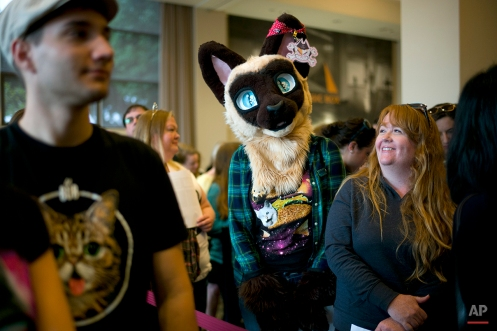 In this Saturday, June 6, 2015 photo, Bryanna Cleland, center, of Fairfield, Calif., wears a cat headpiece while waiting in line to pick up her ticket at the first-ever CatConLA in Los Angeles. (AP Photo/Jae C. Hong)